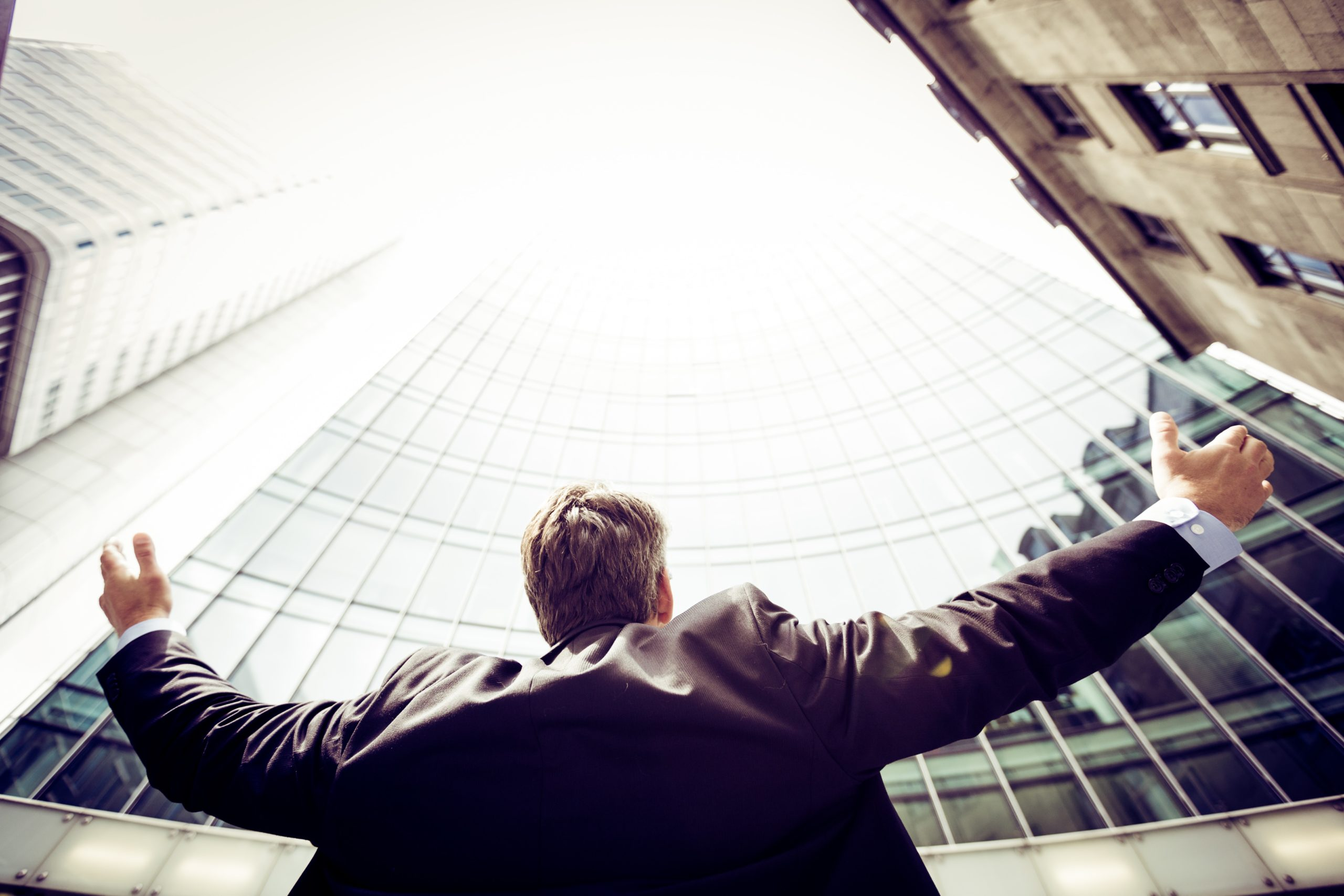 Man with arms up to buildings