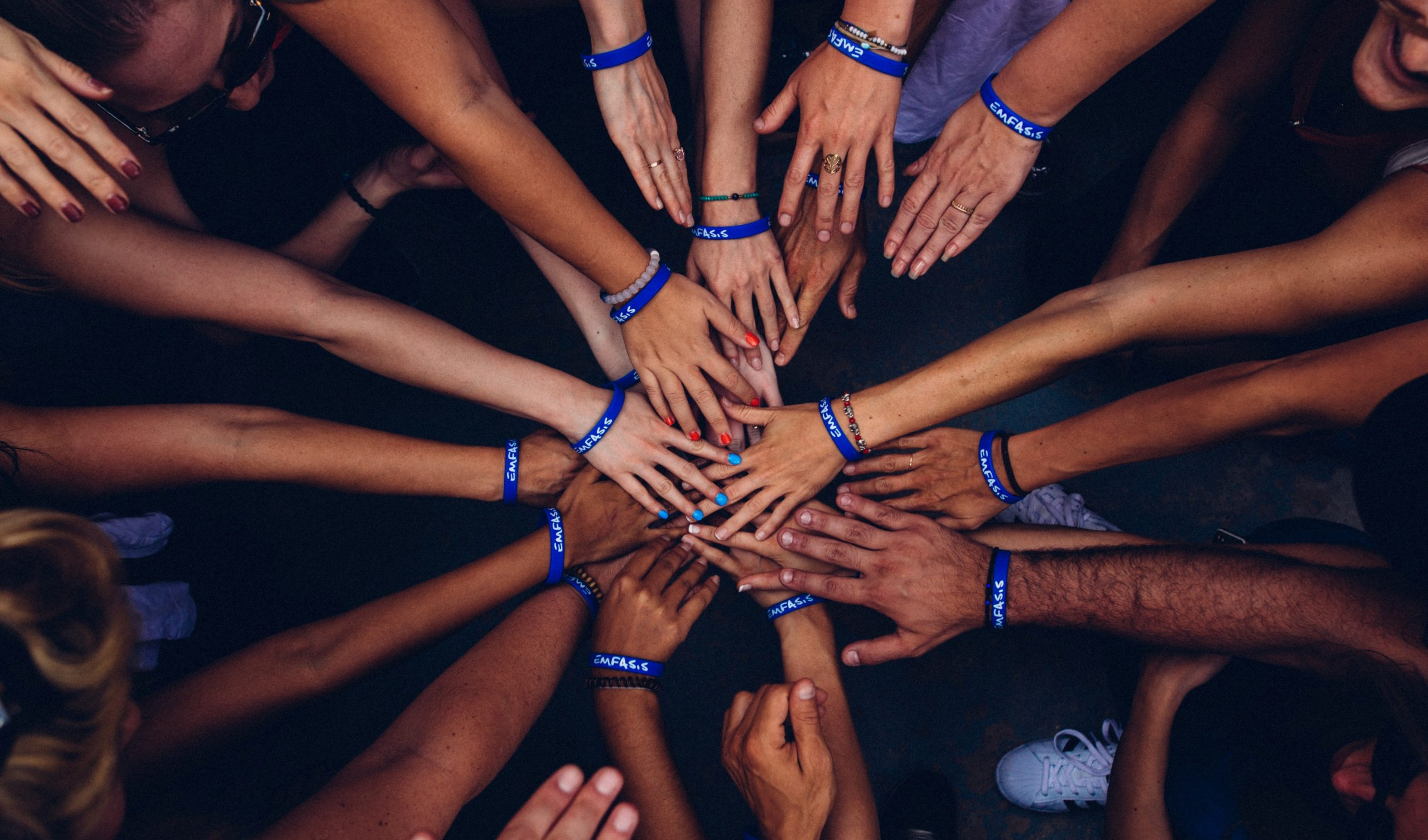 A group of people joining hands in the middle of a group