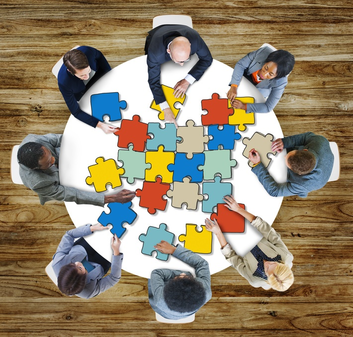 People working together on jigsaw